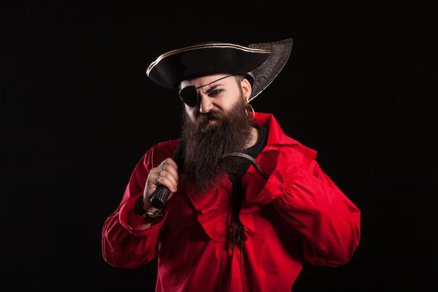 Wütender mann in einem piraten-capitan-kostüm für halloween-holding und axt auf seiner schulter. schöner bärtiger mann mit piratenhut.