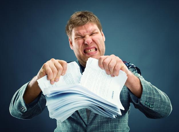 Wütender mann reißt papier heraus