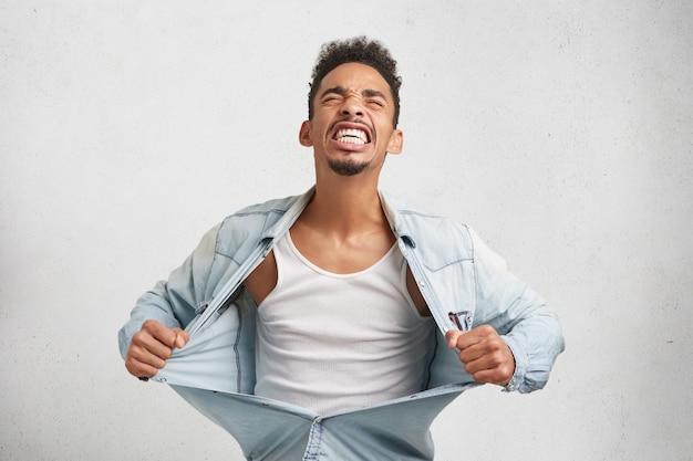 Wütender mann reißt verzweifelt kleider ab, fühlt sich verwirrt und wütend