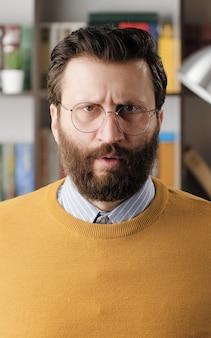 Wütender mann, wut. wütender verärgerter bärtiger mann mit brille im büro oder apartmentzimmer mit blick auf die kamera. nahaufnahme