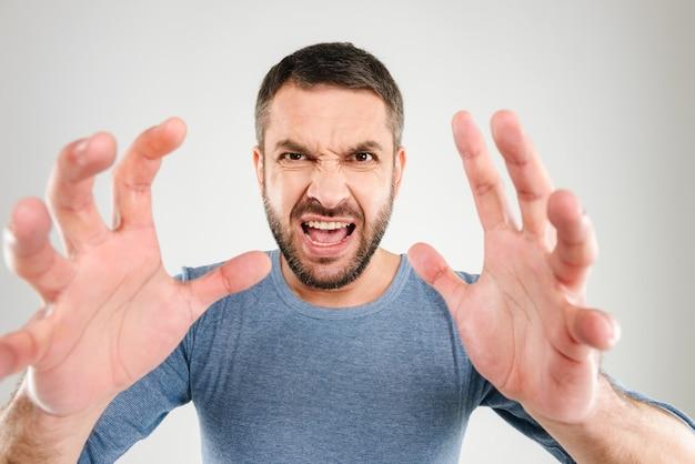 Wütender schreiender missfallener mann, der isoliert steht