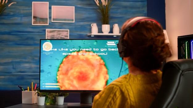 Wütender spieler, der einen wichtigen virtuellen e-sport-wettbewerb des weltraum-shooter-videospiels verliert, das auf einem leistungsstarken computer spielt