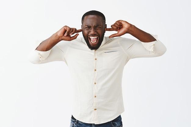 Wütender störter junger mann, der gegen die weiße wand posiert