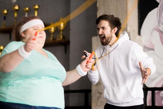 Wütender trainer, der fettleibige frau anschreit