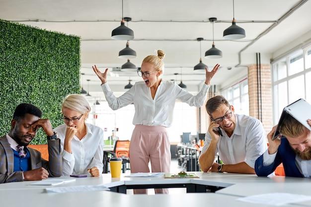 Wütender, unausgeglichener weiblicher chefschrei schimpft mit mitarbeitern, weil sie den plan bei der arbeit nicht erfüllt haben