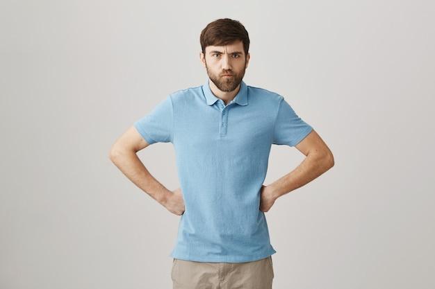 Wütender und enttäuschter junger bärtiger mann posiert