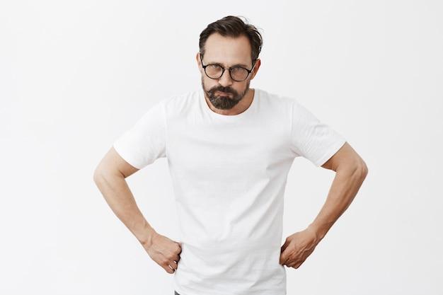 Wütender und mürrischer bärtiger reifer mann mit brille, die aufwirft