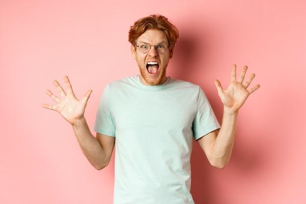 Wütender und unter druck stehender junger mann, der die beherrschung verliert, die hände zur seite spreizt und mit wütendem gesicht schreit und in brille und t-shirt vor rosa hintergrund steht.