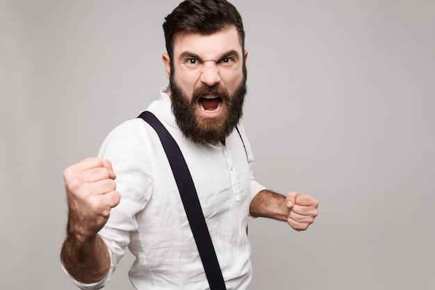 Wütender unhöflicher junger hübscher mann, der über weiß schreit.