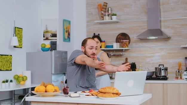 Wütender unternehmer beim frühstück beim arbeiten am laptop in der küche. unglücklicher, gestresster, frustrierter wütender negativer und verärgerter freiberufler im pyjama, der beim morgendlichen essen zu hause schreit. arbeitsproblem