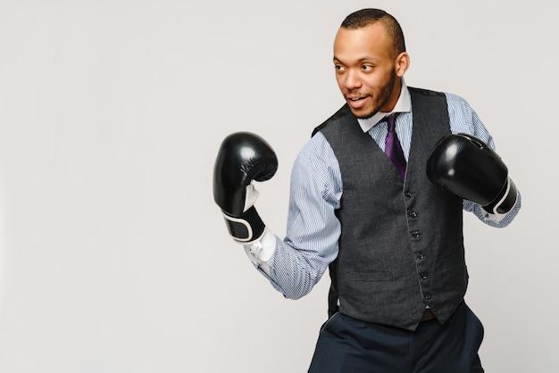 Wütender verärgerter büroangestellter des jungen mannes, geschäftsangestellter, fäuste in der luft mit boxhandschuhen, offenem mund, der schreit und schreit, negatives gefühl gesichtsausdruck gefühl.