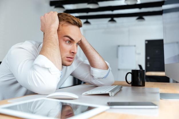 Wütender verzweifelter junger geschäftsmann, der im büro am tisch sitzt