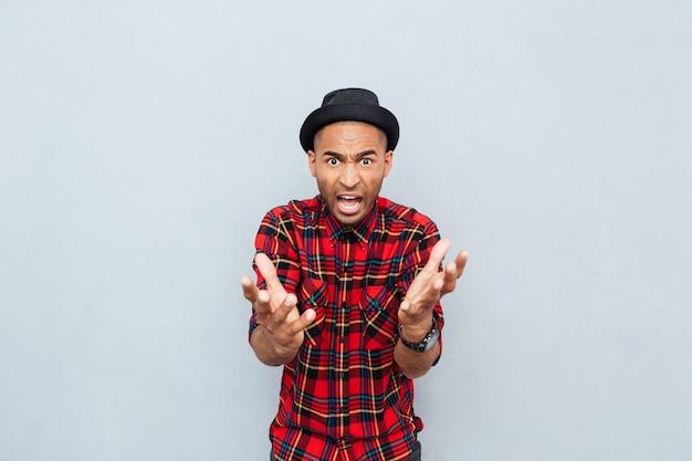 Wütender wütender afrikanischer mann im karierten hemd, der steht und schreit