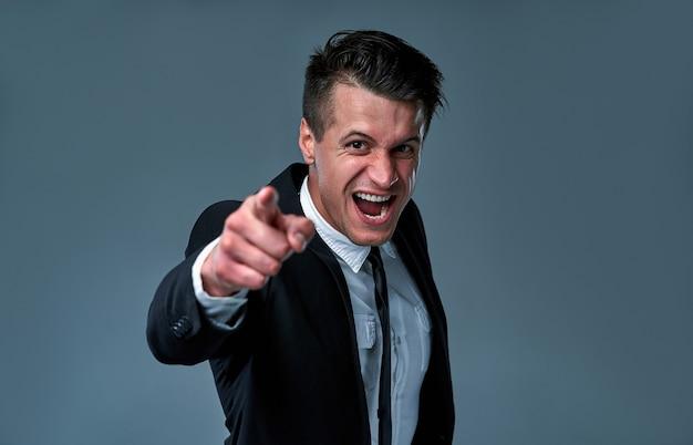 Wütender wütender geschäftsmann im anzug schreit und zeigt mit dem finger auf die kamera isoliert auf grauem hintergrund.