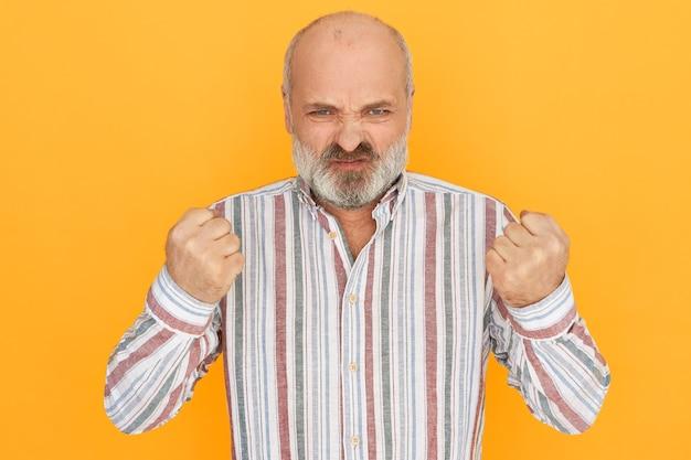 Wütender wütender großvater mit grauem bart verzog das gesicht und ballte die fäuste, um negative gefühle auszudrücken