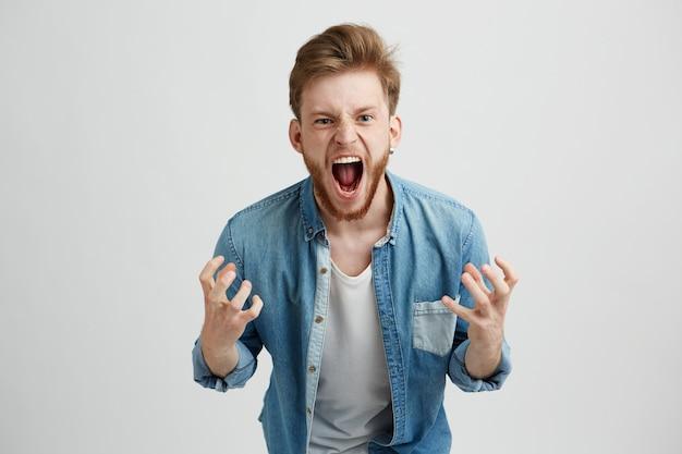 Wütender wütender junger mann mit bart, der schreiend gestikulierend schreit.