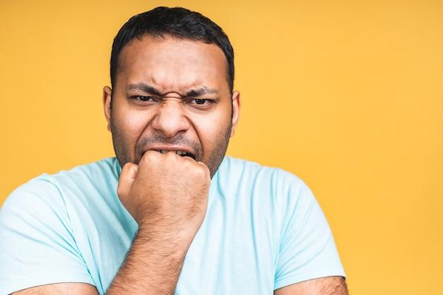 Wütender wütender wütender, verrückter afroamerikanischer indischer schwarzer mann mit mürrischer grimasse im gesicht, mit offenem mund, bereit zu streiten und zu schwören, stärke zu zeigen, einzeln auf gelbem hintergrund.