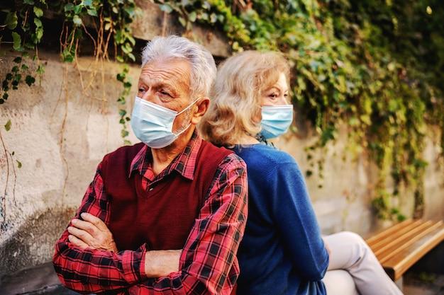 Wütendes älteres paar mit schutzmasken beim sitzen auf der bank rücken an rücken.