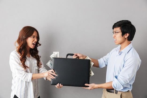 Wütendes asiatisches paar, das isoliert steht und für eine aktentasche voller geldbanknoten kämpft