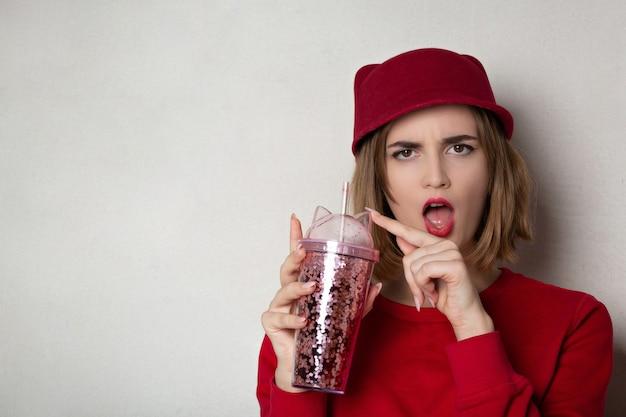 Wütendes brünettes mädchen mit roter mütze und pullover, das cocktail im studio hält. platz für text