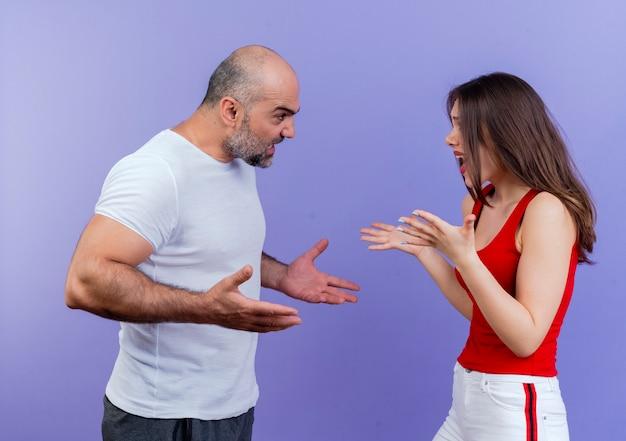 Wütendes erwachsenes paar, das in der profilansicht steht, beide hände ausbreitend und miteinander streitend