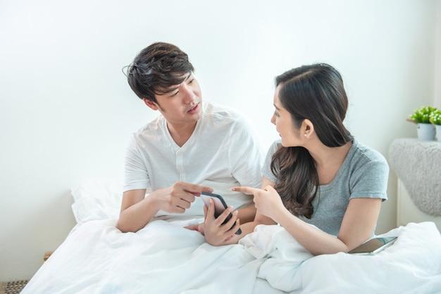 Wütendes junges asiatisches paar oder ehe, die zu hause für ein mobiltelefon kämpfen. eifersüchtige kaukasische frau, die smartphone hält und seinem ehemann nachricht mit argument und unbefriedigter bewegung zeigt.