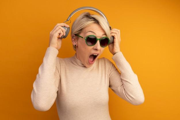 Wütendes junges blondes mädchen mit sonnenbrille, das schreiende kopfhörer abnimmt