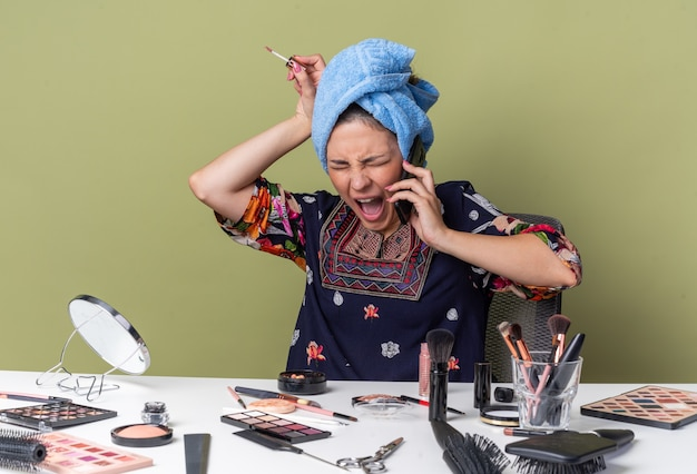 Wütendes junges brünettes mädchen mit eingewickelten haaren im handtuch, das am tisch mit make-up-tools sitzt und jemanden am telefon anschreit und lipgloss hält