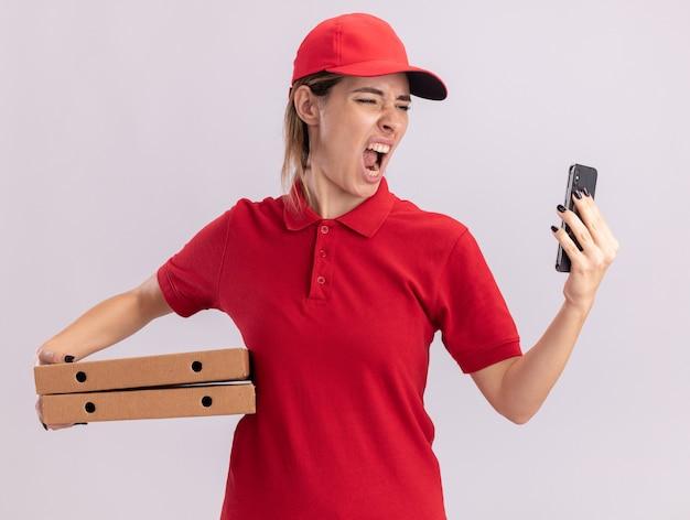 Wütendes junges hübsches liefermädchen in uniform hält pizzaschachteln und schaut auf telefon auf weiß