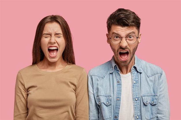 Wütendes junges paar, das gegen die rosa wand aufwirft