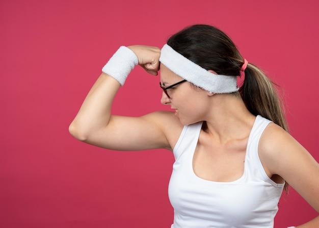 Wütendes junges sportliches mädchen in optischer brille mit stirnband und armbändern verspannt bizeps