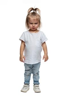 Wütendes kleines mädchen. ein 4-jähriges kind steht in jeans und einem weißen t-shirt. aggression, stress und ressentiments. isoliert auf weißem hintergrund. vertikal.