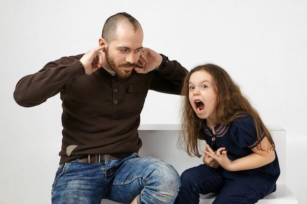Wütendes kleines mädchen mit langen lockeren haaren, die schreien und sich schlecht benehmen. frustrierter junger bärtiger mann, der ohren stopft, kann lästige schreie seiner tochter nicht ertragen