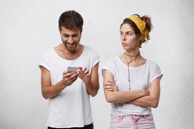 Wütendes mädchen, das die arme verschränkt und ihren fröhlichen freund ansieht, der von mobiltelefonen besessen ist, freunde online benachrichtigt und seine freundin absolut ignoriert.