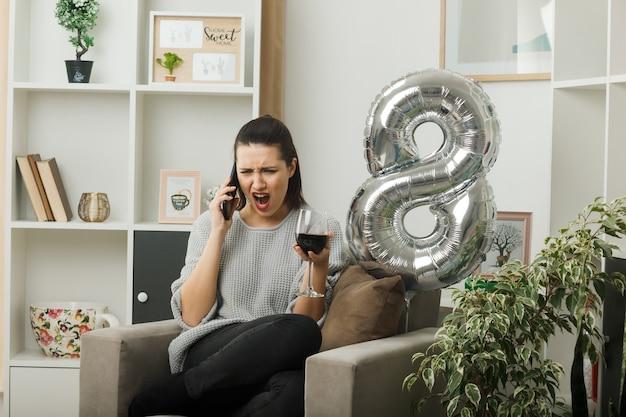 Wütendes schönes mädchen an einem glücklichen frauentag, der ein glas wein hält, spricht über wein, der auf einem sessel im wohnzimmer sitzt