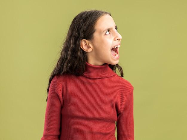 Wütendes teenager-mädchen, das auf olivgrüner wand mit kopienraum isoliert aufschaut und schreit?