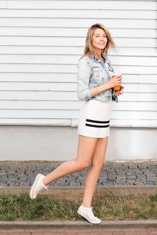 Wunderbare amerikanische junge frau in der trendigen frühlingskleidung in den weißen stilvollen turnschuhen, die spaß auf der straße in der stadt an der wand einer holzwand haben. großartige stimmung. positives mädchen.