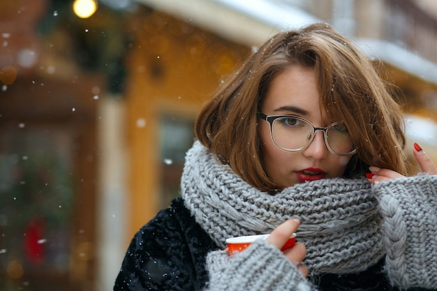 Wunderbare brünette frau trägt strickschal und trendige brillen trinken kaffee auf der straße während des spaziergangs. platz für text