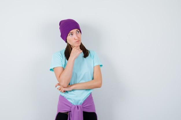 Wunderbare dame, die die hand unter dem kinn in bluse, mütze hält und nachdenklich aussieht, vorderansicht.