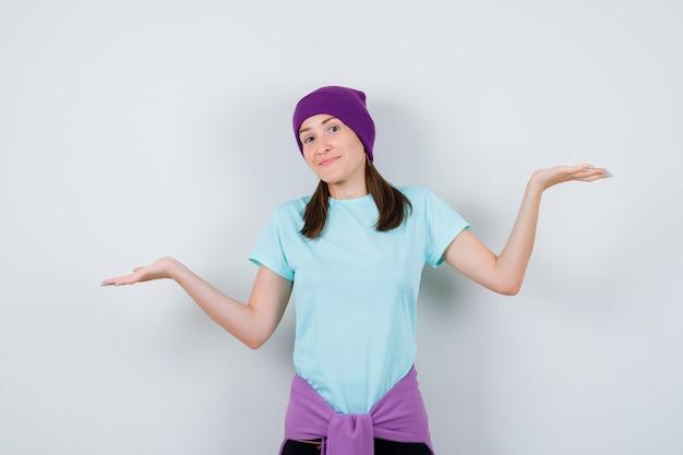 Wunderbare dame, die hilflose geste in bluse, mütze zeigt und zögerlich aussieht, vorderansicht.