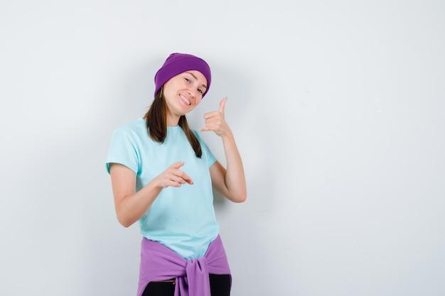 Wunderbare dame, die telefongeste in bluse, mütze zeigt und fröhlich aussieht, vorderansicht.