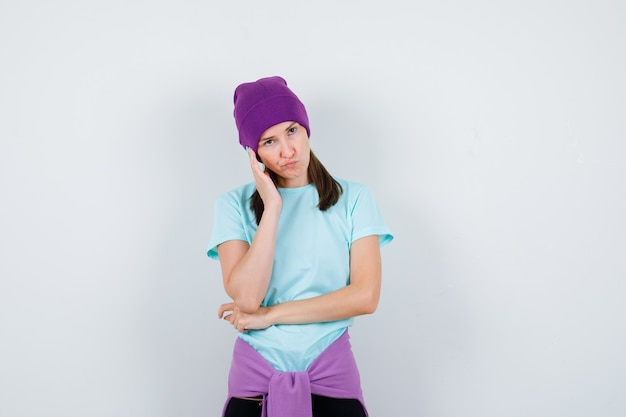 Wunderbare dame in bluse, mütze, die in denkender pose steht und besorgt aussieht, vorderansicht.
