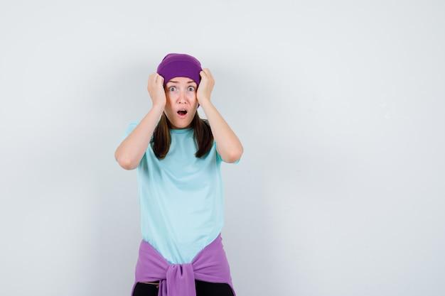 Wunderbare dame in bluse, mütze mit händen auf dem kopf und entsetzt, vorderansicht.