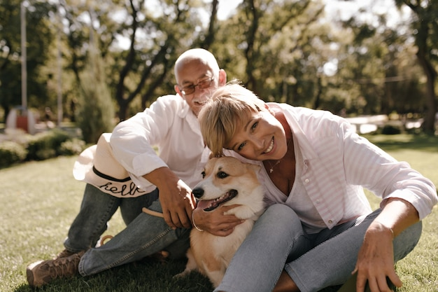 Wunderbare dame mit der blonden kühlen frisur in der gestreiften bluse und in den jeans lächelnd und posierend mit hund und ehemann im weißen hemd im park.