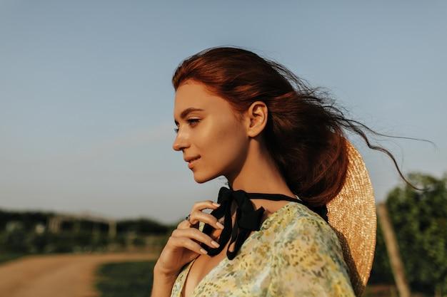 Wunderbare dame mit hellem fuchshaar und schwarzem verband am hals in strohhut und grüner kleidung, die im freien lächelt
