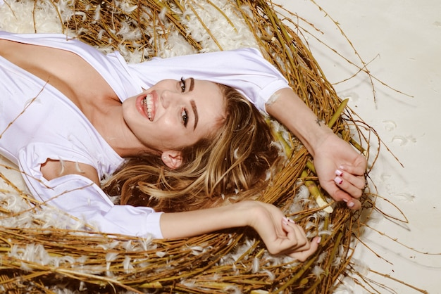 Wunderbare engelsfrau, umgeben von weichen weißen federn. märchen über schönen schwan. nahaufnahme des porträts des schönen jungen modells mit luxus-make-up, das im vogelnest liegt.