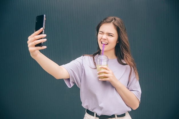 Wunderbare frau, die selfie nimmt und lustige gesichtsausdrücke macht