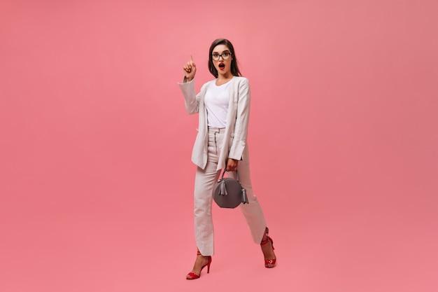 Wunderbare frau im hellen anzug geht auf rosa hintergrund. dame mit roten hellen lippen hat coole idee und bewegt sich auf isoliertem hintergrund.