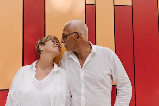 Wunderbare frau mit blonder kurzer frisur in weißen kleidern und brillen, die mit grauem altem mann im hellen hemd auf orange und rot aufwerfen.