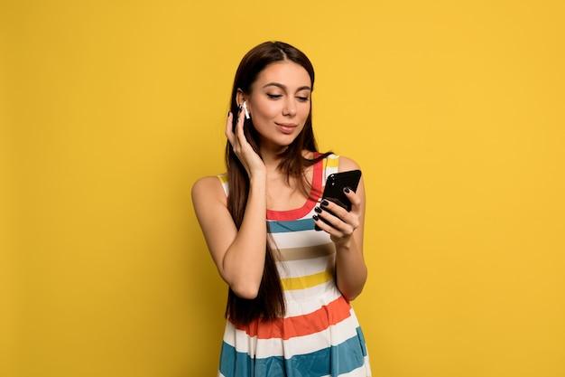 Wunderbare frau mit langen haaren und nacktem make-up, das helles kleid trägt, musik hört und smartphone hält